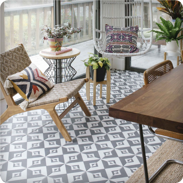 A trendy, well-decorated sitting area bathed in natural light is highlighted by a tiled floor which features the Merola Tile Twenties Vertex tile.