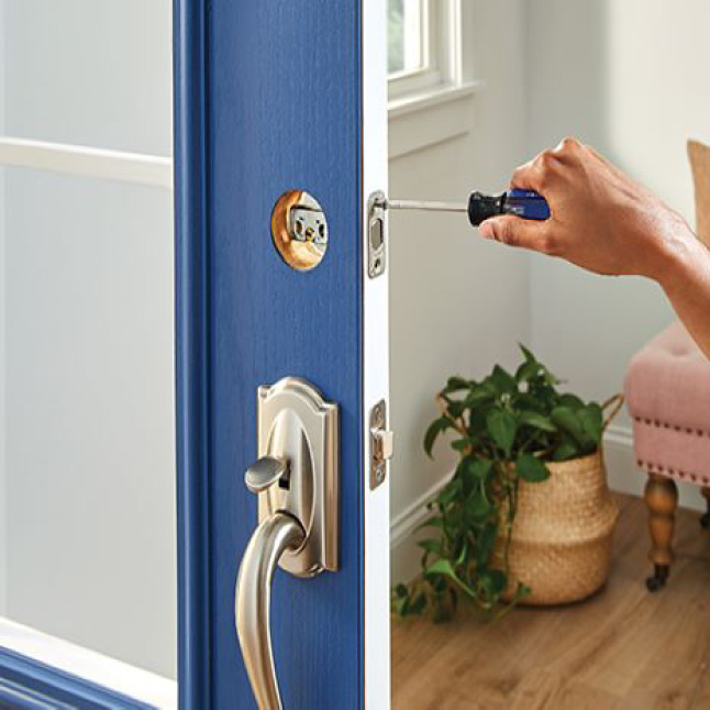 Person using screwdriver to install the deadbolt throw of the Schlage keypad deadbolt on front door.