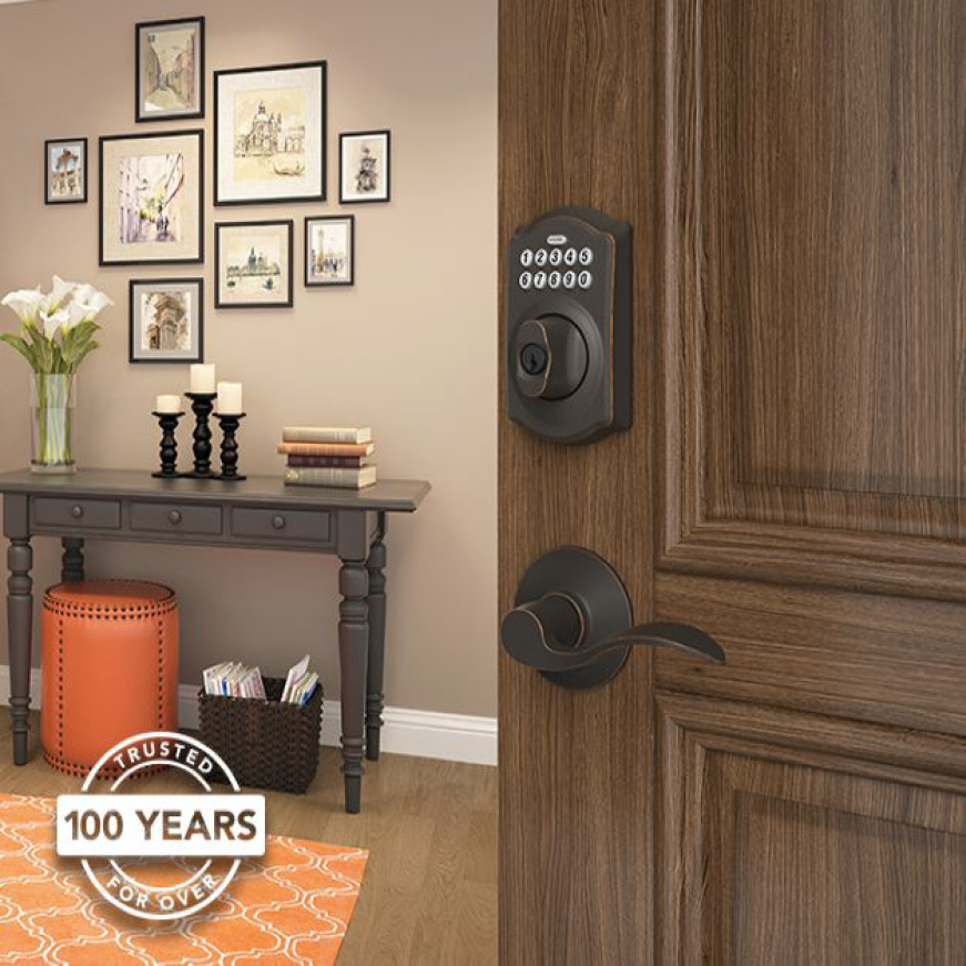 Schlage Camelot Aged Bronze keypad deadbolt with Accent lever on wooden front door.