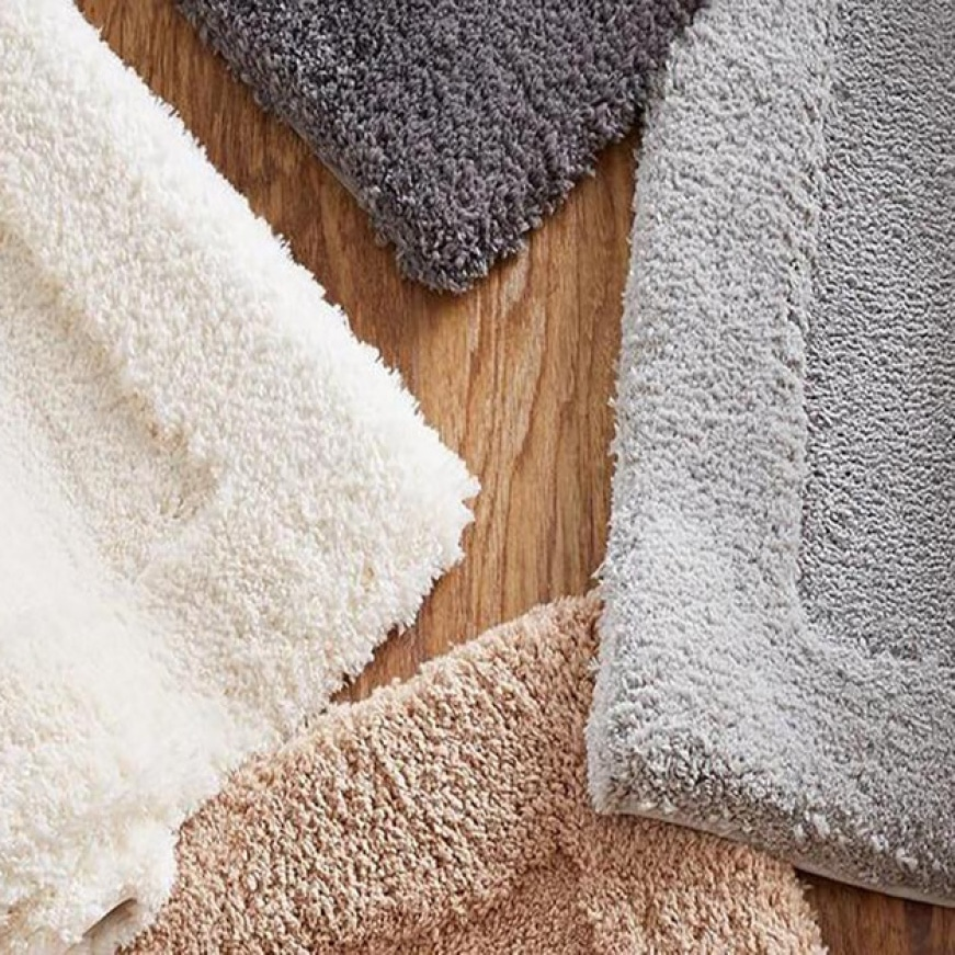 4 bath mats rolled up in a cardinal direction fashion. The bath mats are solid colors (grey, silver, tan, cream) and have a border around the rug.