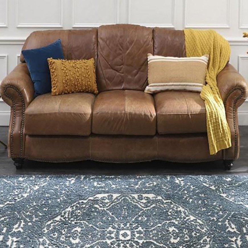 A brown couch is centered in with an array of colorful pillows & a throw blanket. A blue transitional rug is laid out flat on hardwood floors.