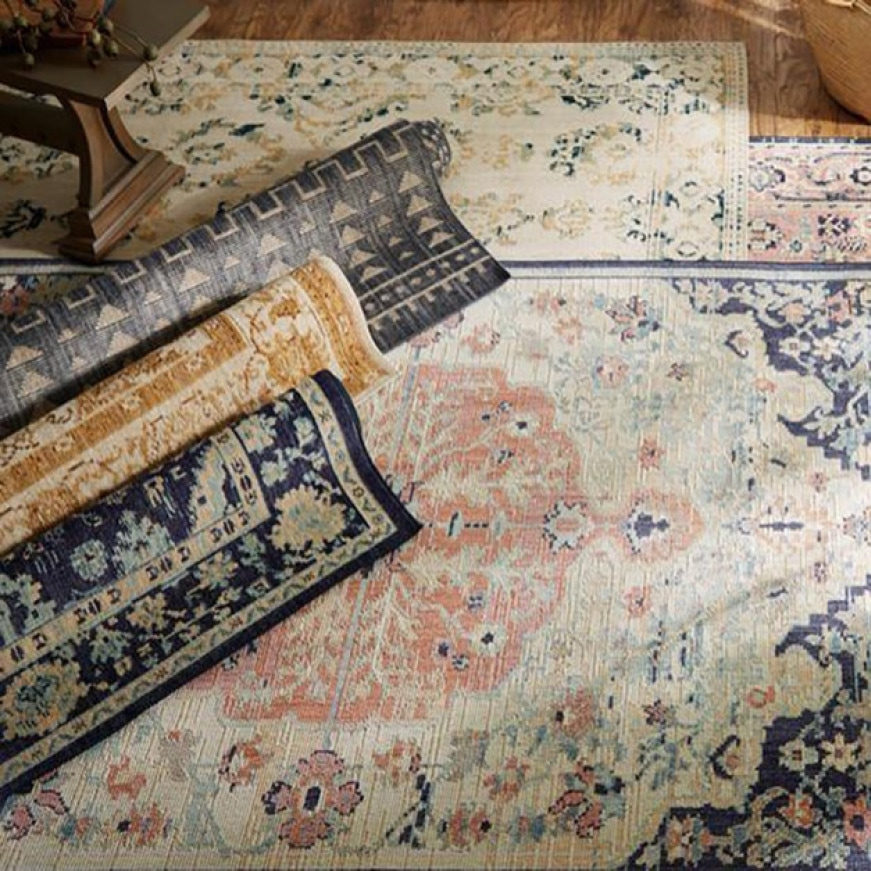 3 rugs are laid out flat and the other 3 are rolled on hardwood. Image invokes a neutral tone with a color palette of salmons blues creams and yellows