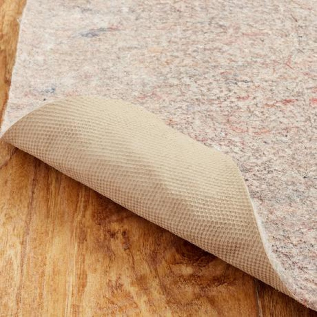 A rug pad sits on a hardwood floor with the corner pulled back showing the latex backing.