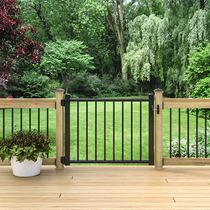 A view looking outward to a yard featuring the deck gate installed on a pressure treated deck