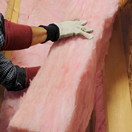 close-up of hands installing pink fiberglass insulation in a wall cavity