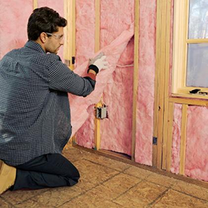 Man installing pink fiberglass insulation in a wall cavity