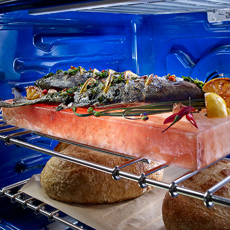 Angled interior view of the oven with a fish roasting on the upper rack and two loaves of bread baking on the lower rack.
