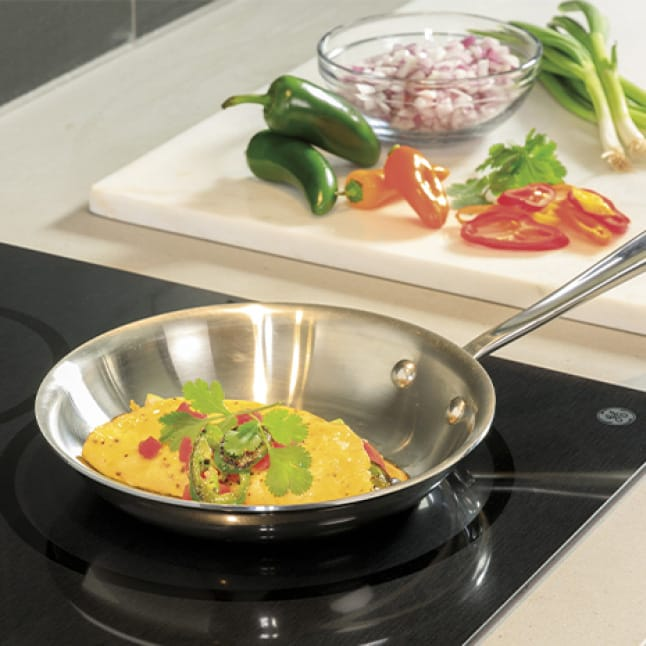An omelet cooks on the cooktop. An assortment of vegetables and garnishes sit to the side on a cutting board.