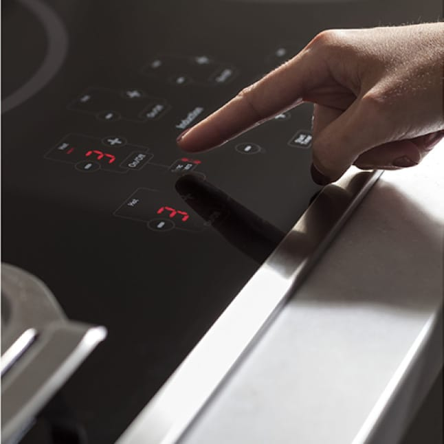A finger adjusts the heat on the cooktop