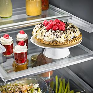 Four desserts standing on a glass refrigerator shelf.