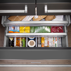 Freezer drawer fully extended with top two tiers stepped out above. Each level is filled with frozen items.
