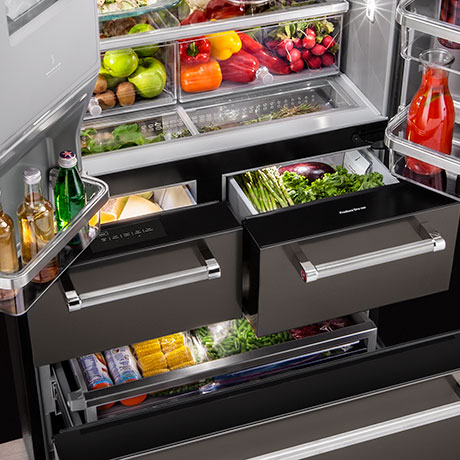 Fully open refrigerator stocked with fresh fruits and vegetables. Two exterior drawers are partially open below the doors.
