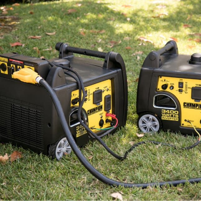 Lifestyle image of two 100233 inverter generators in use with a parallel kit