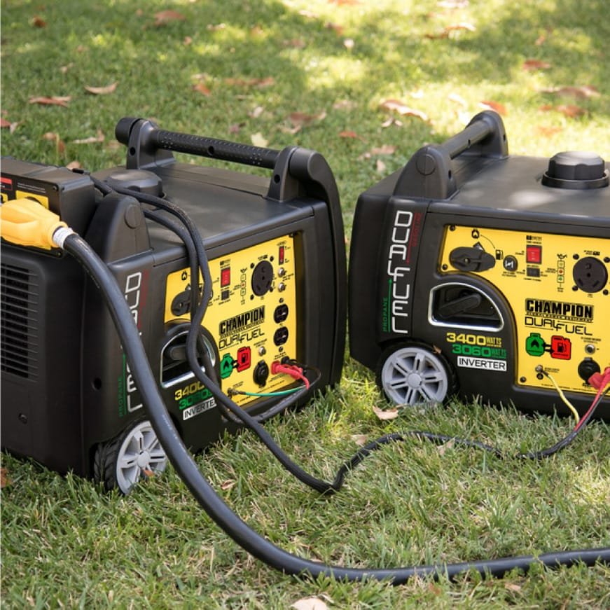 Lifestyle image of two 100263 inverter generators in use with a parallel kit