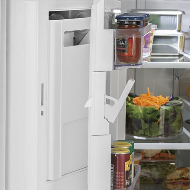The internal shelves of the fridge have been pulled away from the door to reveal its hidden ice maker.