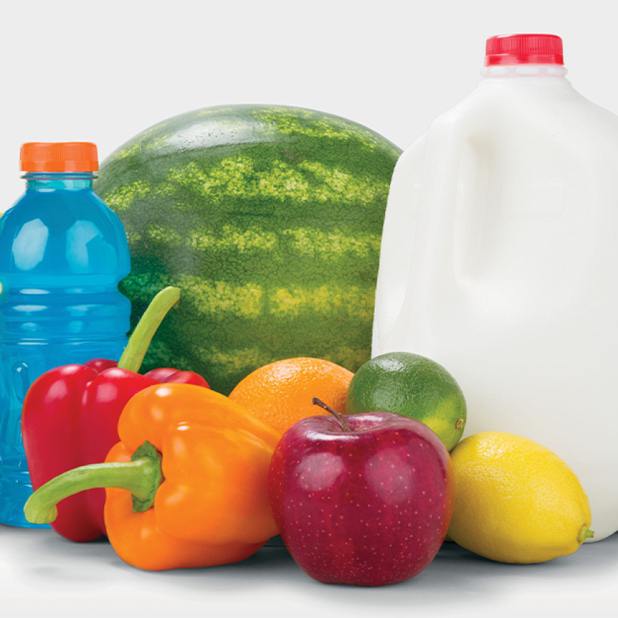 A variety of food sits on a white backdrop. Apples, peppers, and citrus are arranged in front of a sports drink, a gallon of milk, and a watermelon
