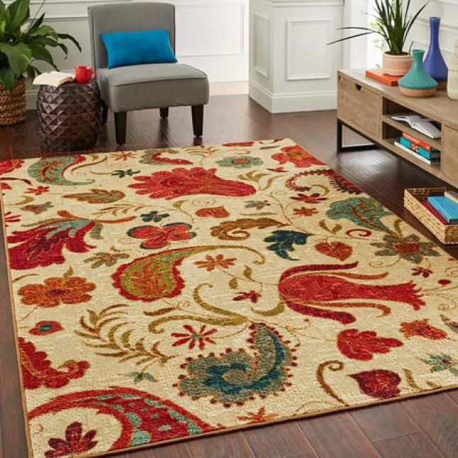 A large tan rug with red & teal floral elements is shown in the center of a sitting area with contemporary furniture.