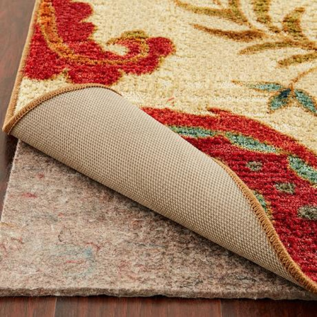 Image shows the top of the rug design with the corner of the rug being pulled back to expose the rug pad underneath.