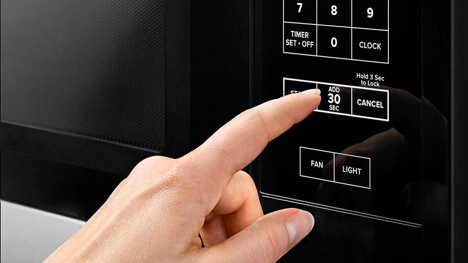 A hand presses the Add 30 Seconds button on the microwave's control panel.