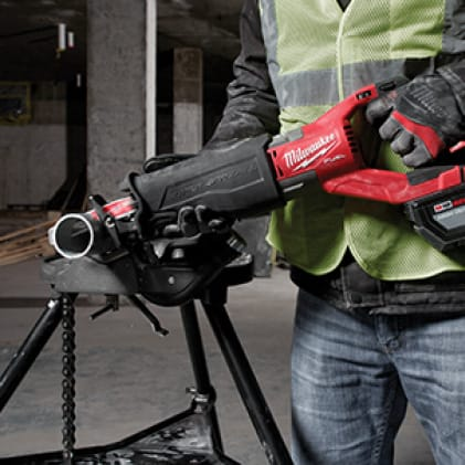 Man wearing hi-vis vest and work gloves uses the M18 FUEL SAWZALL reciprocating saw to cut metal pipe.