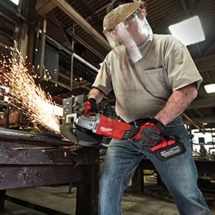 Man wearing gloves and face shield uses the M18 FUEL Braking Grinder on metal as sparks fly.