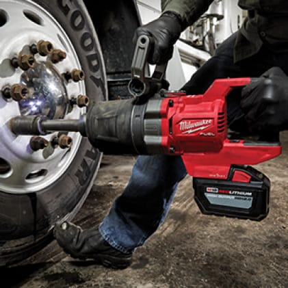 Man with work gloves on uses the M18 FUEL D-Handle High Torque Impact Wrench to remove lug nut.