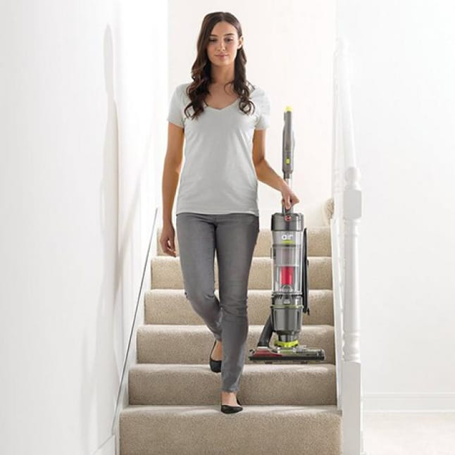 Woman carrying the Lightweight Air Steerable Vacuum Cleaner down the stairs with ease.
