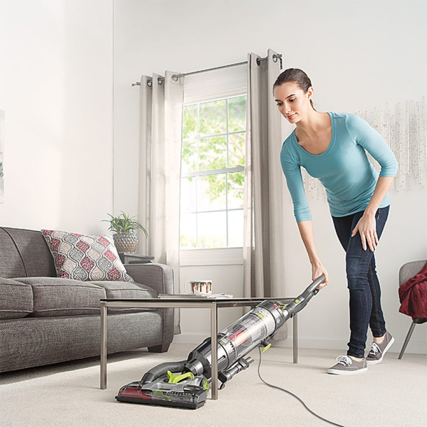 Air Steerable Pet Bagless Upright Vacuum Cleaner cleaning living room carpet with ease.