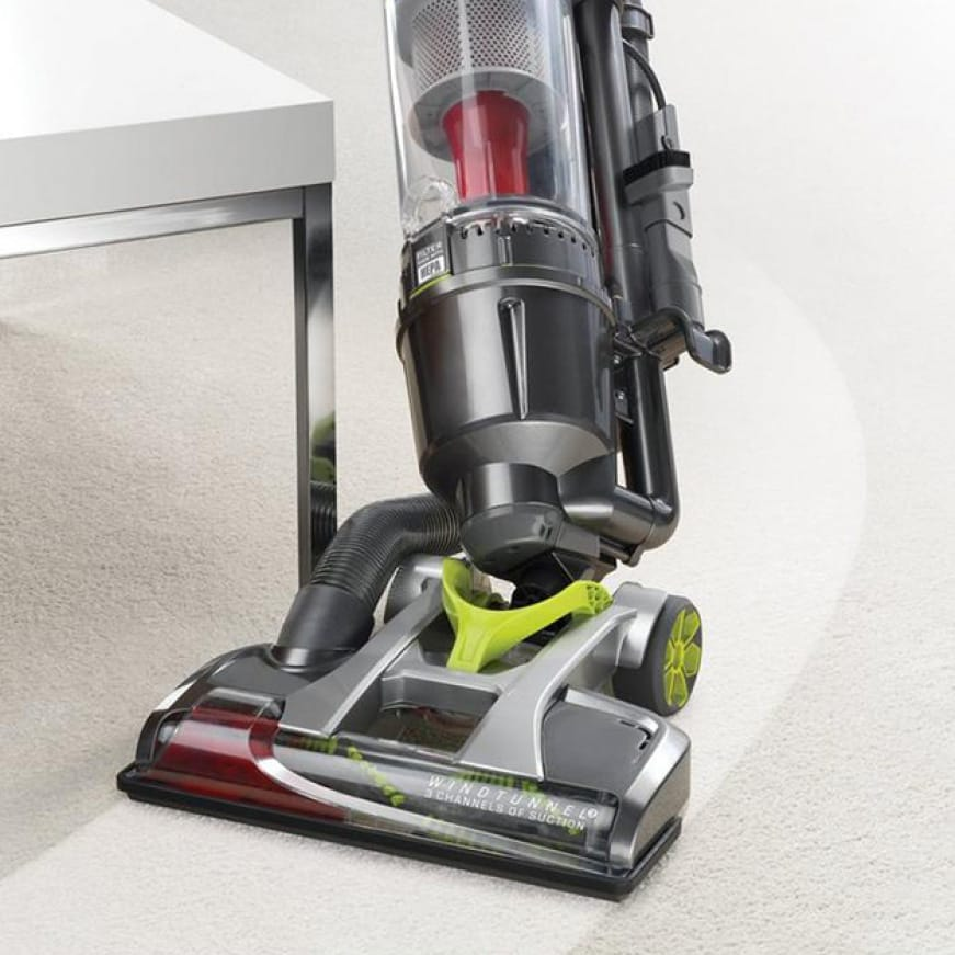 Air Steerable Pet Bagless Vacuum Cleaner effortlessly swiveling around furniture obstacle.