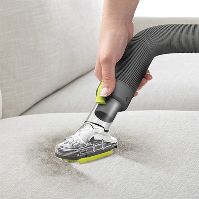 Air Steerable Pet Vacuum Cleaner with Specialized Upholstery Tool in use on a sofa.