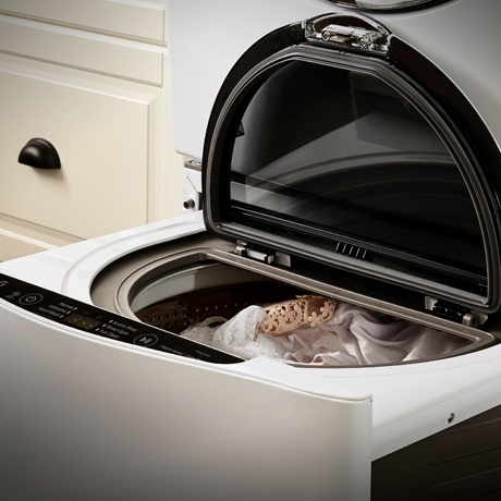 Close up front view of the LG SideKick Pedestal Washer with the lid open and delicates inside