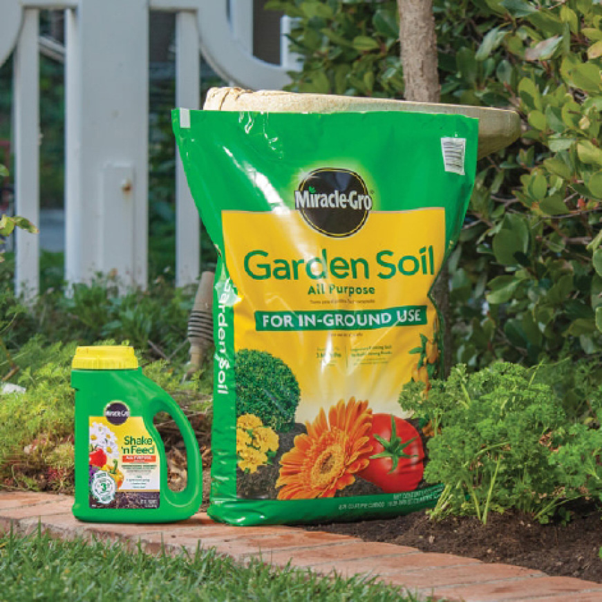 Miracle-Gro Garden Soil All Purpose For In-Ground Use and Miracle-Gro Shake 'n Feed Plant Food in garden bed
