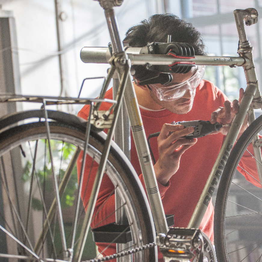 Image of man working on bike with rotary tool