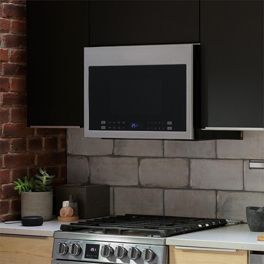 Visual of a small stainless steel over the range built-in microwave in kitchen cabinets