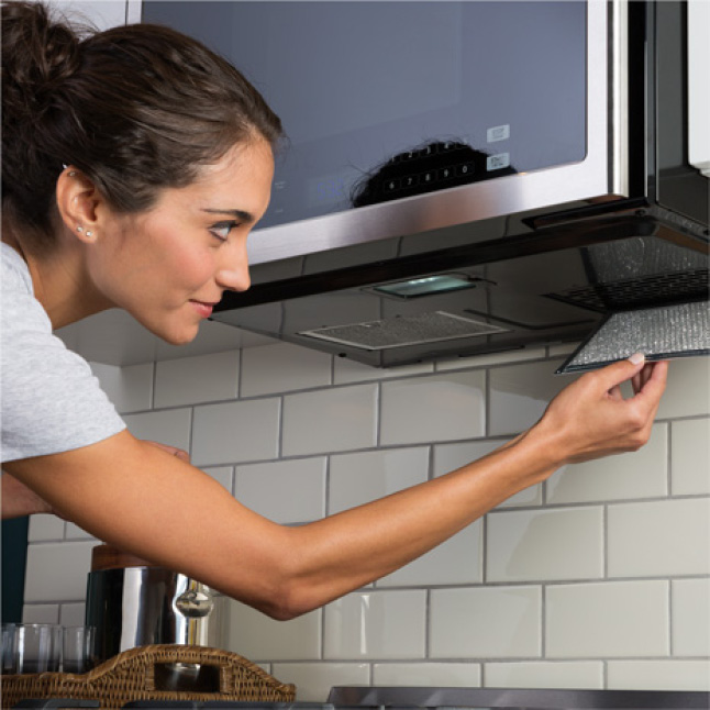 Image of woman pulling charcoal filter out of the stainless steel over the range microwave