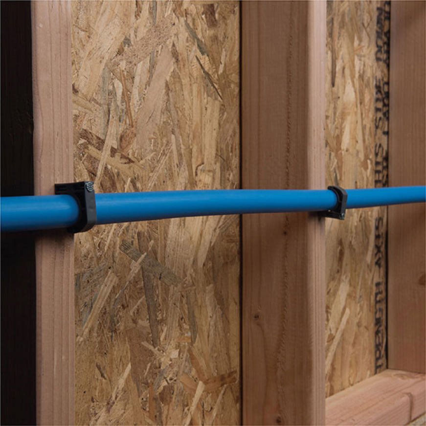 Piping secured to wall with clamps