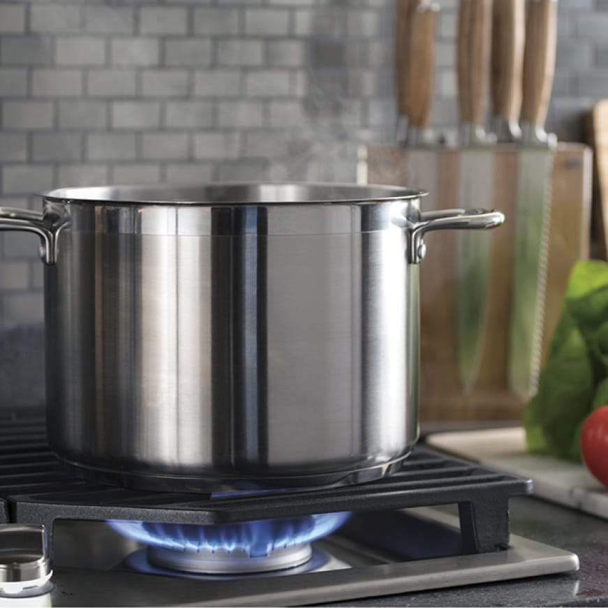 Image of tall stock pot on cooktop with power boil burner on and flame ignited