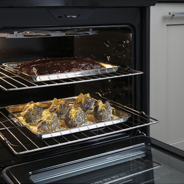 Two metal racks with food baking on them are pulled halfway out of the oven's spacious cavity. The oven door has been lowered.