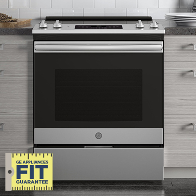 A General Electric stainless steel stove fits perfectly between two gray counters. A logo in the corner reads GE Appliances Fit Guarantee.