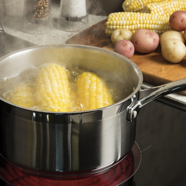 A pot boils corn in water on the dual-size glass cooktop. More corn and potatoes sit on a cutting board in the background.