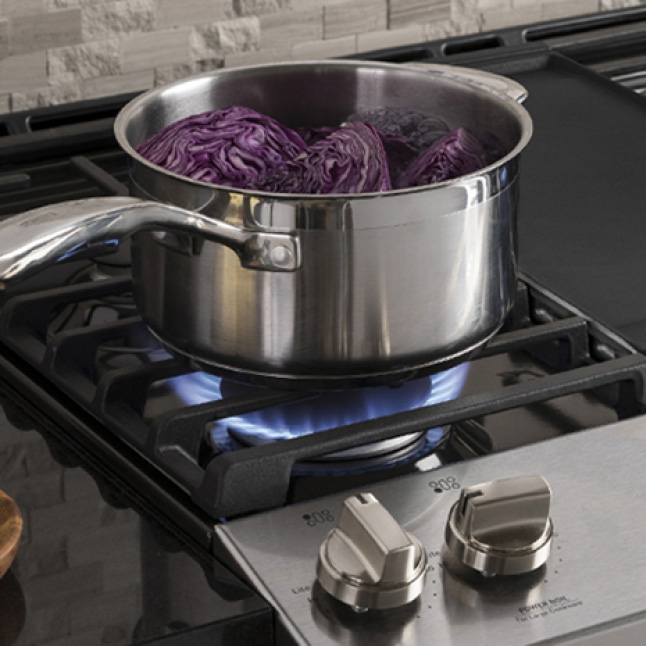Red cabbage boils inside a stainless steel pot over the gas burner.