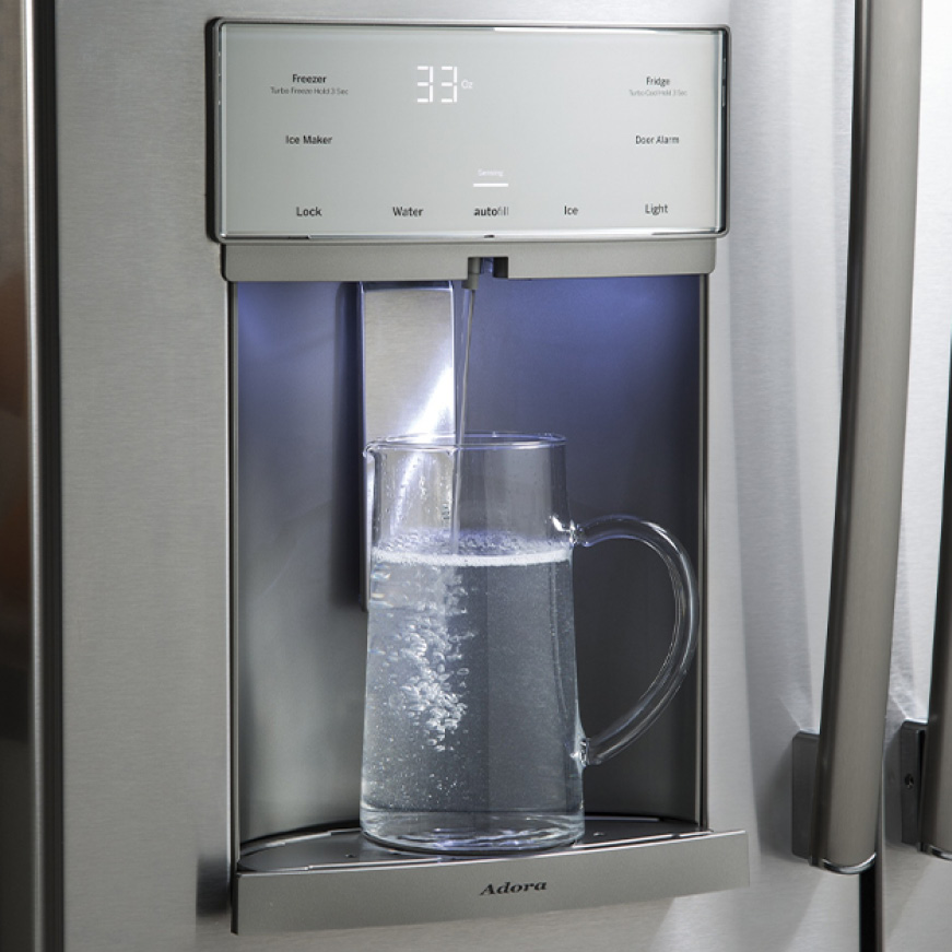 A glass pitcher sits underneath the fridge's water dispenser. A stream of water steadily fills the container.