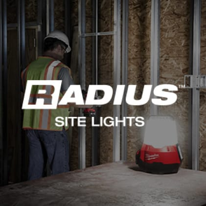 A man works on jobsite with portable RADIUS Site Light on table nearby.
