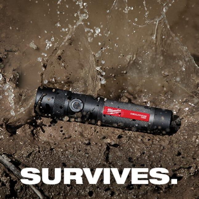 A Milwaukee flashlight lays on dirt surface.