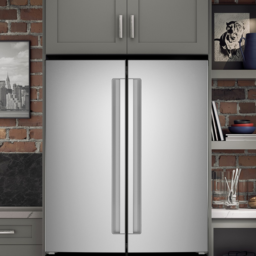 A close up of the front of the refrigerator, fitting flush with the surrounding cabinetry