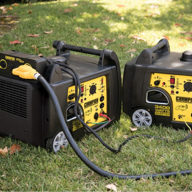 Lifestyle image of two 100261 inverter generators in use with a parallel kit