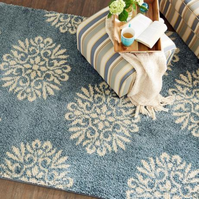 An overhead shot shows a chair and ottoman on top of a rug that has exploded, cream medallions on a blue background.