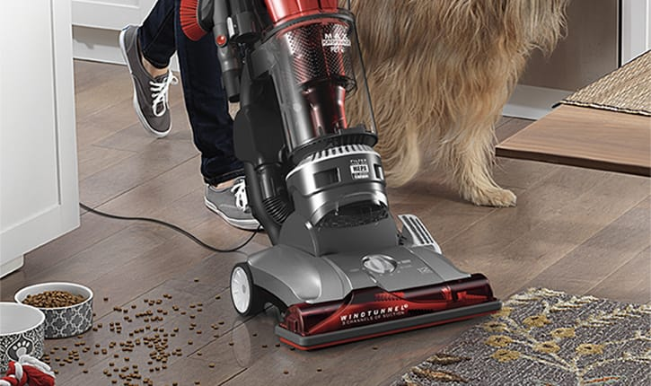 A woman using the Hoover WindTunnel 3 Max Performance Pet Upright Vacuum in a living room cleaning up dirt from a knocked over plant.
