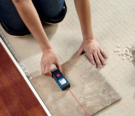 Bosch GLM165-10 being used to calculate square footage on tile.