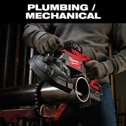 Man in jeans, gray long sleeve shirt and work gloves uses a band saw to cut a metal pipe.